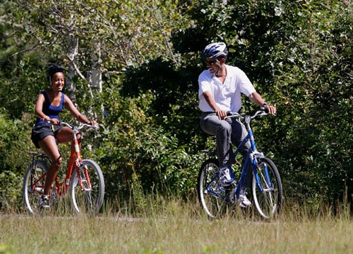 President Barack Obama, and daughter Malia, ride bicycles