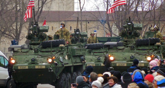 US Army soldiers travel in American armored combat vehicles through the streets of Narva, Estonia, during a military parade to mark the country's Independence Day.