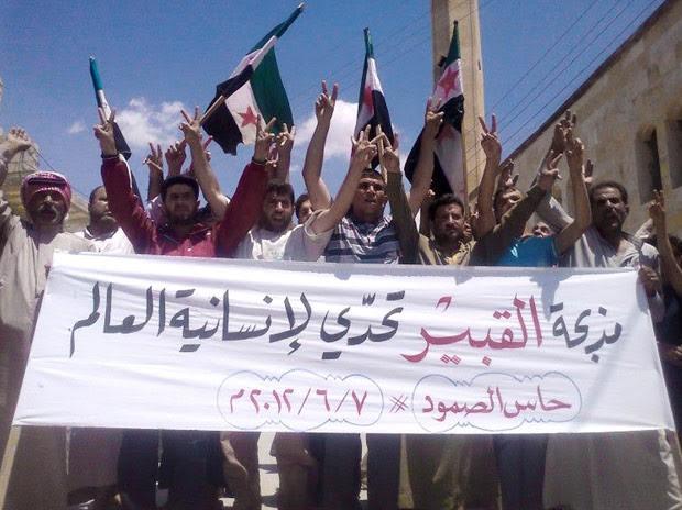 Manifestantes protestam nesta quinta-feira (7) em Hass, na província síria de Idlib, contra o massacre da véspera (Foto: AP)