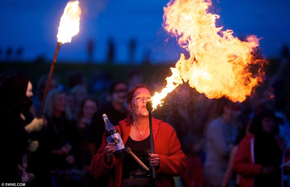 Fiery display: A fire-breather gets into the spirit of the summer solstice at Avebury stone circle