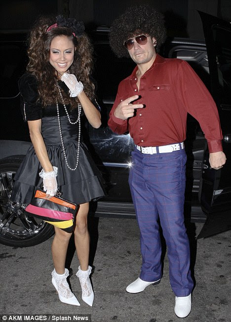 Retro style: Nick Lachey sported a Seventies-style Afro while his fiancée Vanessa Minnillo was an Eighties throwback as they attended a Hollywood party last night