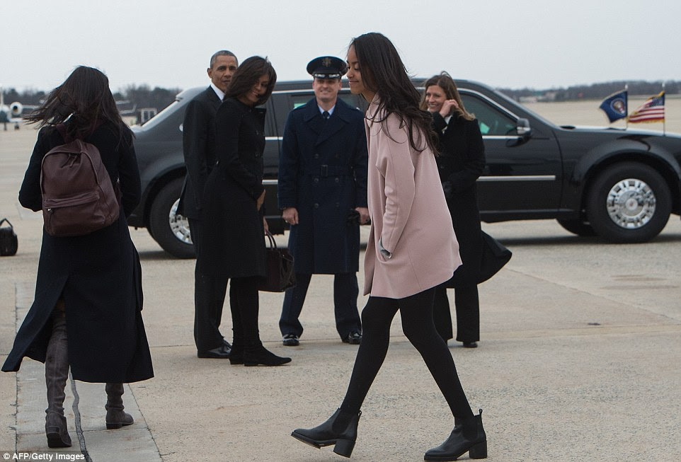 Malia Obama (center) walks behind her sister Sasha (left) as they prepare to board the plane to Cuba on Sunday afternoon