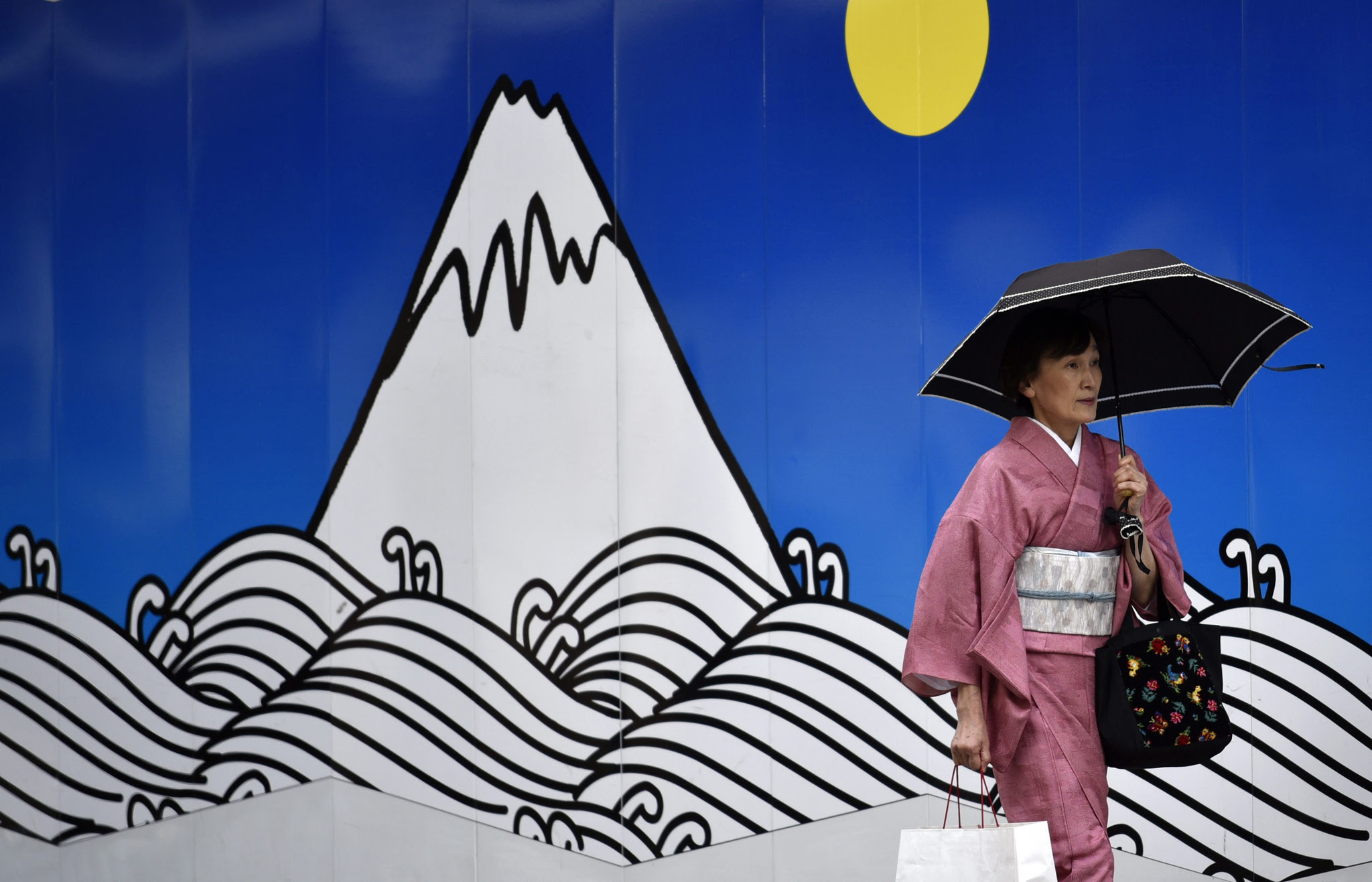 epa05393789 A woman clad in a kimono walks in front of a decorated construction site wall at Ginza shopping district in Tokyo, Japan, 27 June 2016. Tokyo stocks rebounded after dropping sharply on 24 June following the Brexit vote. The Nikkei Stock Average gained 357.19 points, or 2.39 percent, to close at 15,309.21.  EPA/FRANCK ROBICHON