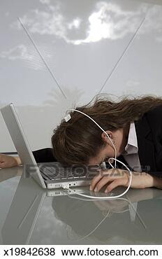 Stock Photo - young woman plugged  into lap top,  sleeping on desk.  fotosearch - search  stock photos,  pictures, images,  and photo clipart