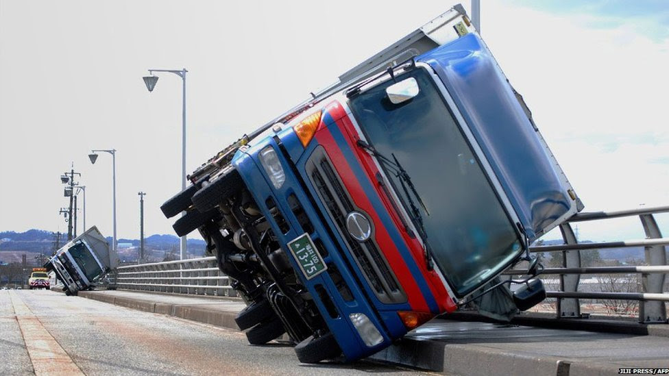 Two trucks lie on their sides on a bridge at Toyama city, western Japan