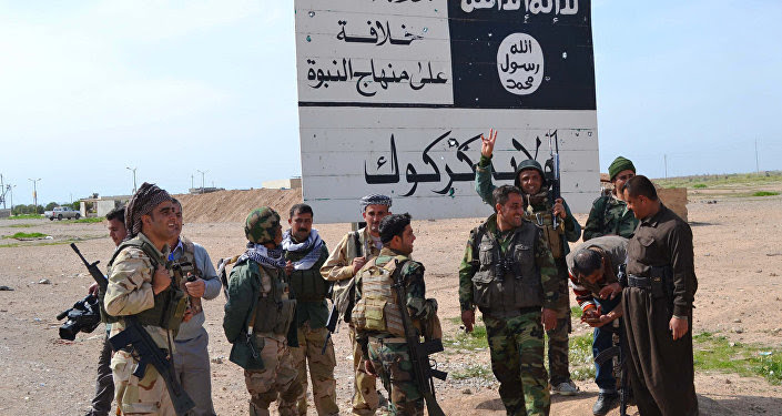Iraqi Kurdish Peshmerga fighters stand next to an Islamic State (IS) group sign at the entrance to the northern Iraqi town of Hawija, south of Kirkuk on March 9, 2015 after they reportedly re-took the area from IS jihadists