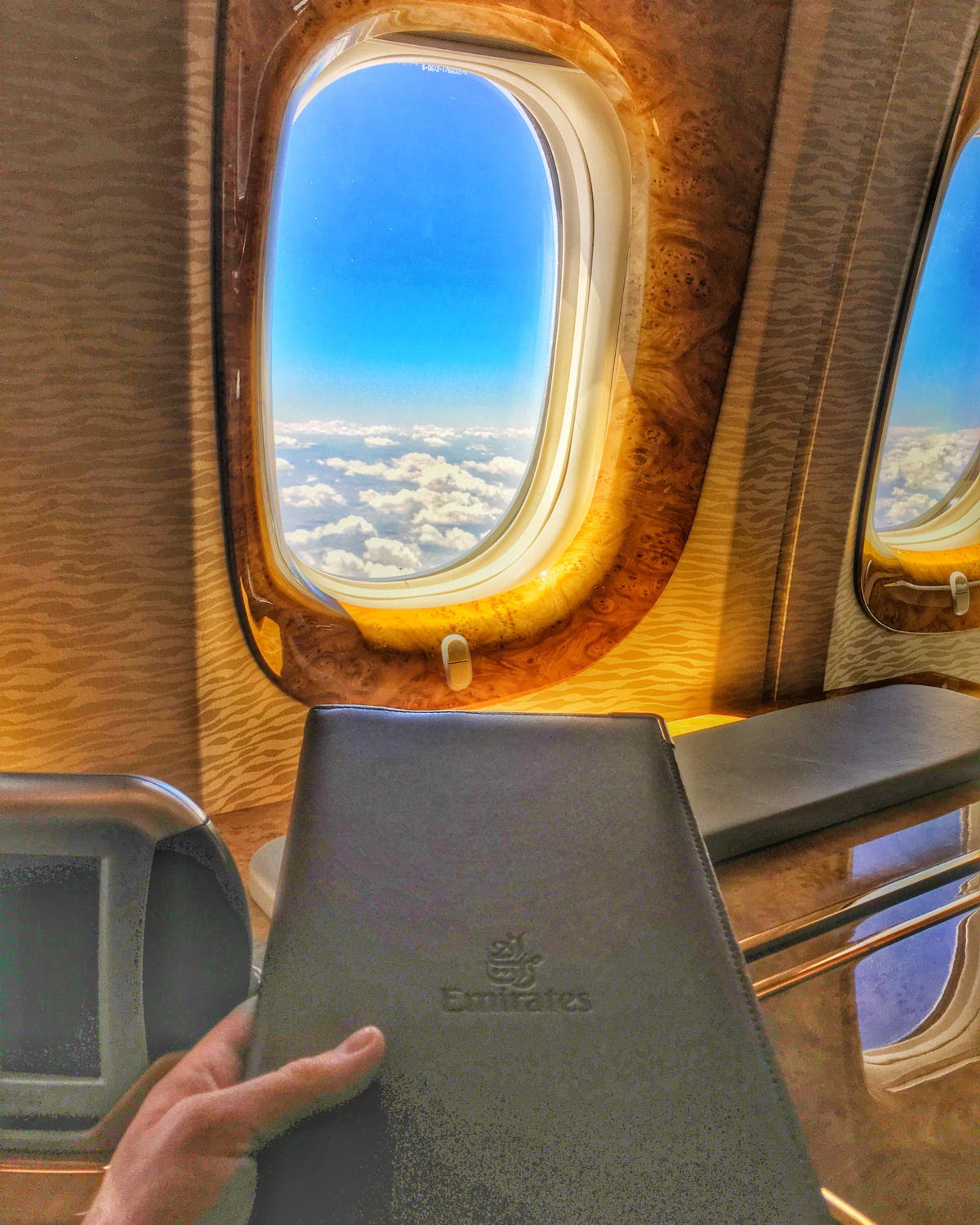 The glossy wood paneling and gold trim provide the perfect frame for the view outside. First class on an Emirates Airbus A380 has only 14 seats, so the service is tailored to each person.