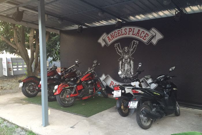 Black wall with 'Angels Place' logo and mural of bikie, with several motorcycles parked in front