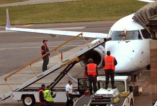Mecânicos fazem vistoria após o acidente nesta terça-feira (24) no aeroporto de White Plains (Foto: AP)