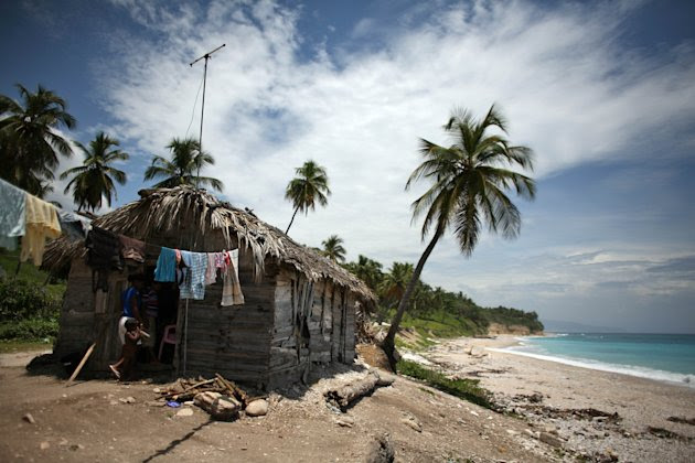 Two people walk into a thatched roof hut located along the shore in Barahona, Dominican Republic, Thursday, Aug. 23, 2012. Puerto Rico and the U.S. Virgin Islands braced for torrential rains on Thursday as Tropical Storm Isaac whipped up waves as high as 10 feet (3 meters) in the Caribbean and threatened to become a hurricane that could take a shot at Florida just as Republicans gather for their national convention. (AP Photo/Ricardo Arduengo)