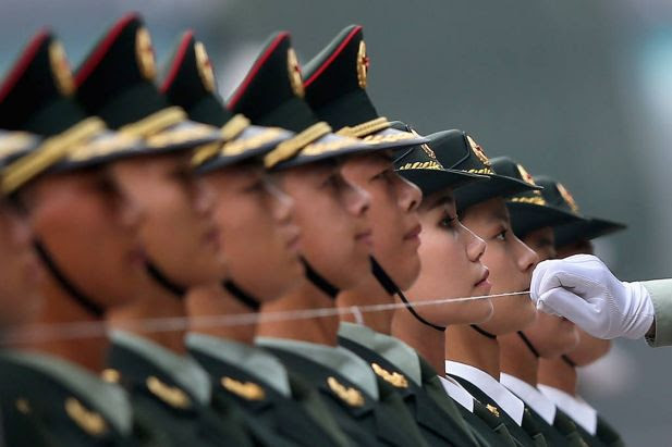 Members of a Chinese People's Liberation Army honour guard line up behind a string, which is used to make sure that they are standing in a straight line, before a welcoming ceremony for German Chancellor Angela Merkel outside the Great Hall of the People on July 7, 2014 in Beijing, China.