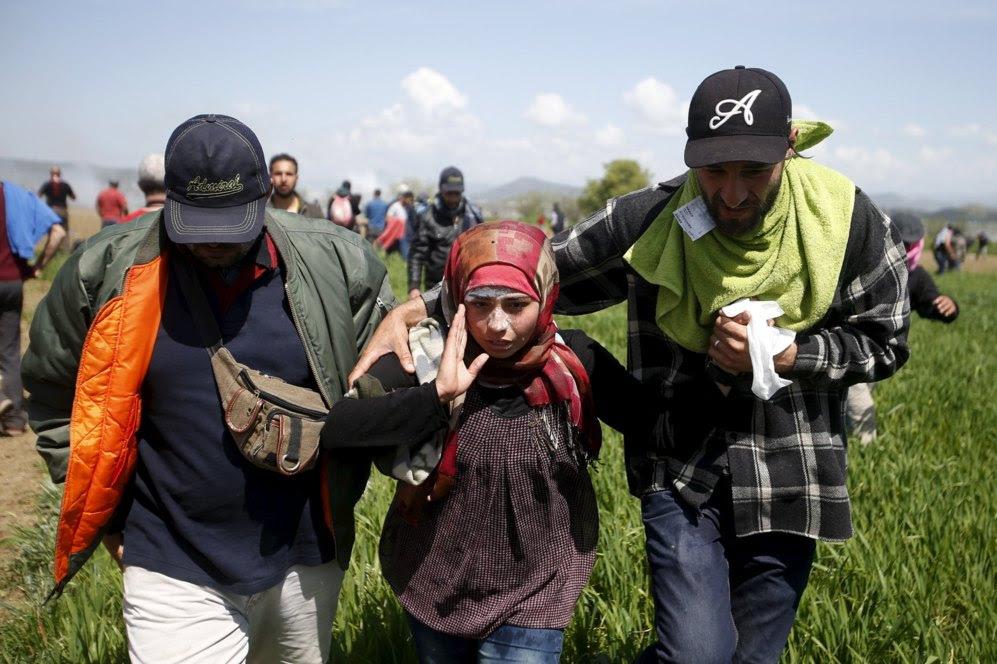 Varios participantes en la protesta se retiran tras verse afectados por el gas lacrimógeno.