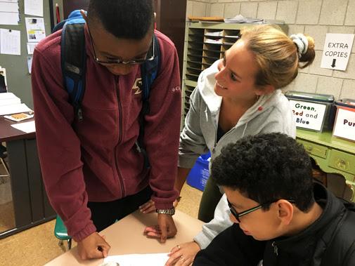 Eighth-grade math teacher Kendal Schwarz with students Didio DaCosta Jr. and Leo Martins.