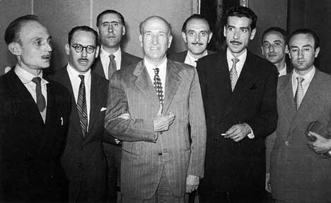 Fotografía en blanco y negro de José Hierro posando con otros siete hombre, todos de traje y corbata