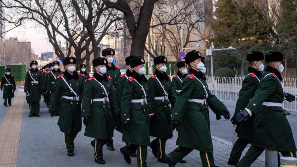 大疫冲击政局,涉北京防务的军方关键人物接连异动。图为一队军警戴着口罩行走在北京街头。