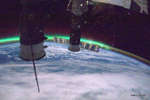 With Russian-made Progress and Soyuz vehicles in the foreground, the ISS flies away from an aurora, on April 2, 2010.