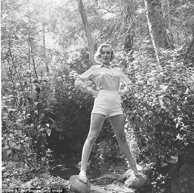 Rainha da Floresta: Vestido em um shorts e camisa de cor clara, Marilyn está com as mãos nos quadris e as pernas montado em um par de pedras de cada lado de uma cachoeira muito pequeno