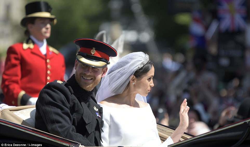 Harry sonríe a la multitud mientras Meghan saluda a los espectadores durante la procesión después de la boda real en Windsor