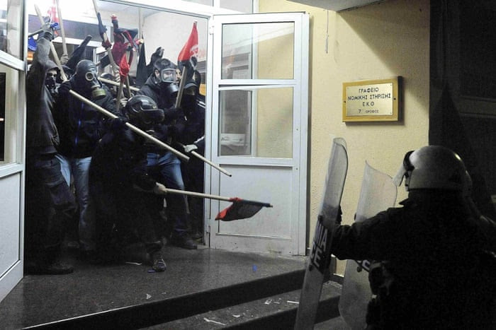 Riot police clash with masked youths occupying the labour centre in Thessaloniki, Greece. Police fired teargas to disperse protesters, who hurled petrol bombs and set light to banks. The violence broke out during marches marking the sixth anniversary of the fatal police shooting of unarmed 15-year-old Alexandros Grigoropoulos in Athens