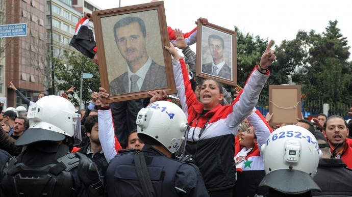 Pro-Assad Syrians demonstrate outside the meeting hall as foreign ministers from dozens of countries gather to set conditions for a new Syria, pushing for tighter sanctions and diplomatic pressure to further isolate President Bashar Assad, while urging the opposition to offer a democratic alternative to his regime, in Istanbul, Turkey, Sunday, April 1, 2012. The show of solidarity at the Friends of the Syrian People conference in Istanbul, was marred by the absence of China, Russia and Iran, key supporters of Assad who disagree with Western and Arab allies over how to stop the bloodshed. (AP Photo)