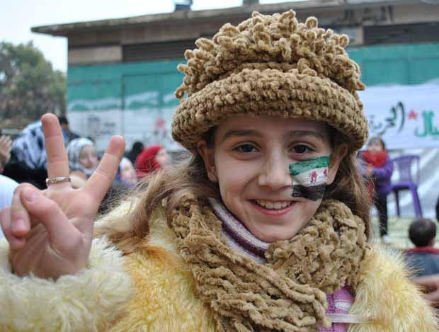Menina participa de ato contra o presidente da Síria, Bashar al Assad, em Khalidya, na província de Homs, nesta quinta-feira (26) (Foto: AP)
