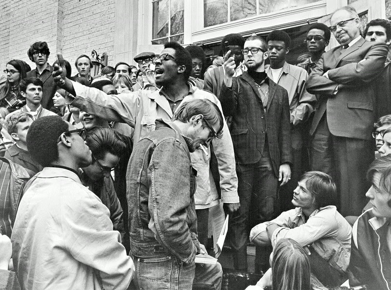 Description of  APR 17 1969 - Paul Chambers, of the Black Student Alliance at CSU, tells a crowd estimated at 500, that President Morgan, right, with arms folded, apparently doesn't understand demands presented to administration. Morgan told audience on grounds at Administration building, more money would be needed to meet stated goals. (Barry Staver/The Denver Post)