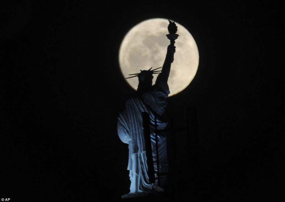 Replica: The full moon provides a stunning backdrop for Kosovo's answer to New York's Statue of Liberty on top a hotel in the capital Pristina this evening