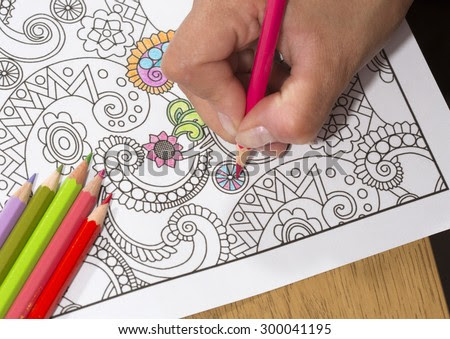 An image of a new trendy thing called adults coloring book. In this image a person is coloring an illustrative and detailed pattern for stress relieve for adults. - stock photo