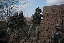 Soldiers beside a mud wall