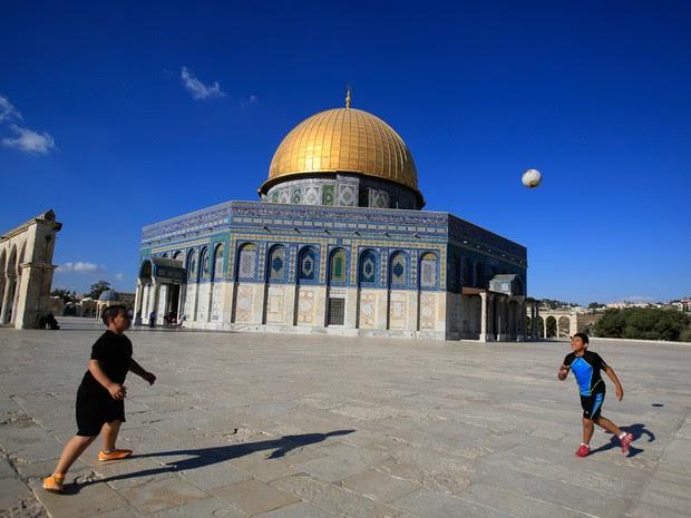 Meninos palestinos jogam futebol em frente à mesquita Domo da Rocha em Al-Aqsa, na cidade antiga de Jerusalém (Foto: Hatem Moussa/AP)