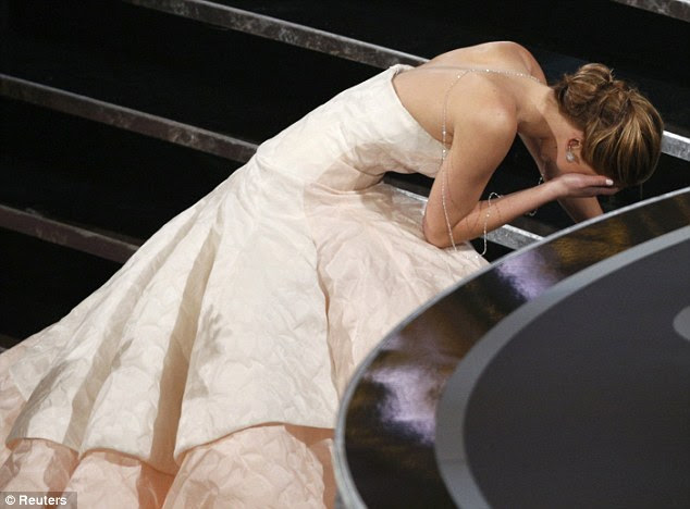 Oh no! Jennifer Lawrence falls to the floor after tripping on her floorlength gown as she climbed the stairs to accept her Best Actress Oscar in Hollywood on Sunday night