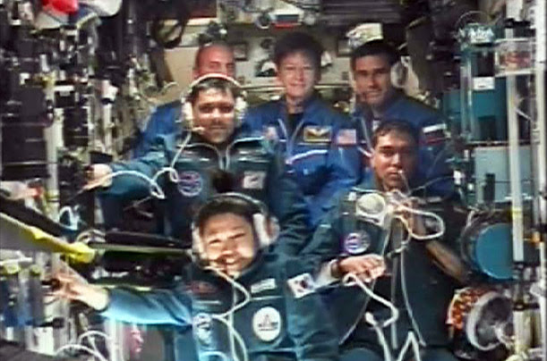 American, Russian and Korean astronauts aboard the International Space Station listen to a call from mission control in Russia in April.