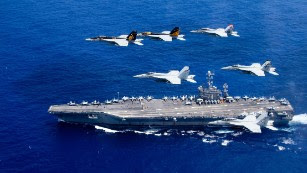 <strong>F/A-18 Hornets fly above the Nimitz-class aircraft carrier USS John C. Stennis in the Pacific Ocean. The US Navy has 10 of the 97,000-ton ships, which can carry more than 60 aircraft each.</strong>