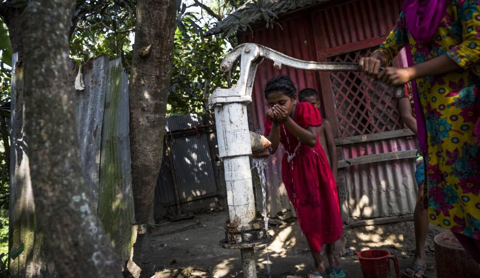 Una niña bebe de un pozo contaminado con arsénico en Totar Bagh, Bangladesh.