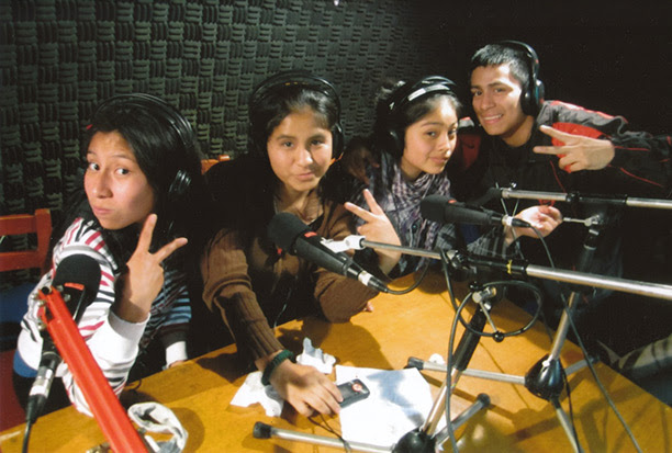 Three girls and a boy are sitting at a desk in a recording studio with microphones in front of them.