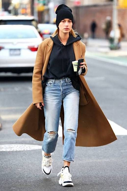 Le Fashion Blog Hailey Baldwin Off Duty Black Beanie Camel Wool Coat Black Hoodie Distressed Jeans Ugly Shoe Trend Louis Vuitton Sneakers Via Who What Wear