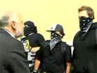 The YouTube video shows Dave Coles, president of the Communications, Energy and Paperworkers Union, ordering three masked men back from a line of riot police.