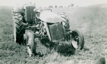 Ford tractor after having flipped over. Behind it is a 1948 Case tractor.