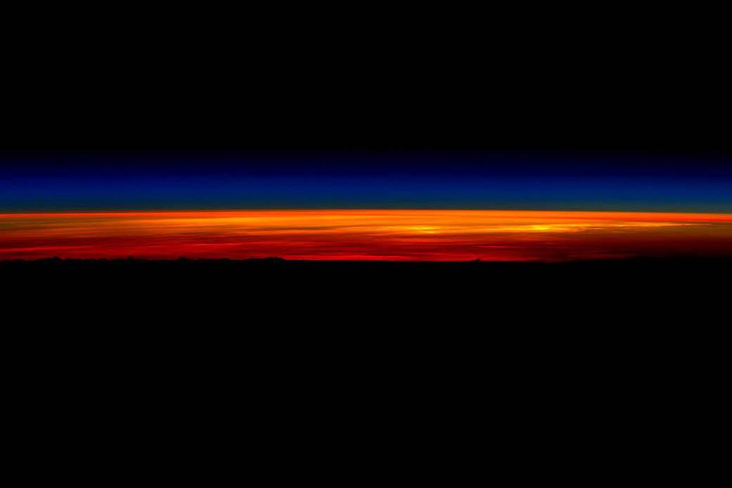 Beginning of sunrise over dark horizon