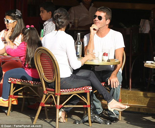Cowell adopts a thoughtful pose while Ms. Silverman drinks from a glass of mineral water