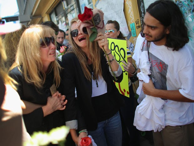 Jacqueline Llach (à esq.) e Offir Hernández (à dir.), respectivamente mãe e irmã do grafiteiro colombiano Israel Hernández, choram durante protesto contra a morte do jovem, que recebeu um disparo de taser da polícia em Miami (Foto: Joe Raedle/Getty Images/AFP)