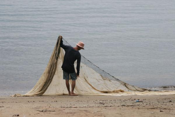 Photograph of Fishermann arranging his nets on the beach near Ban Phe - Thailand - Asia