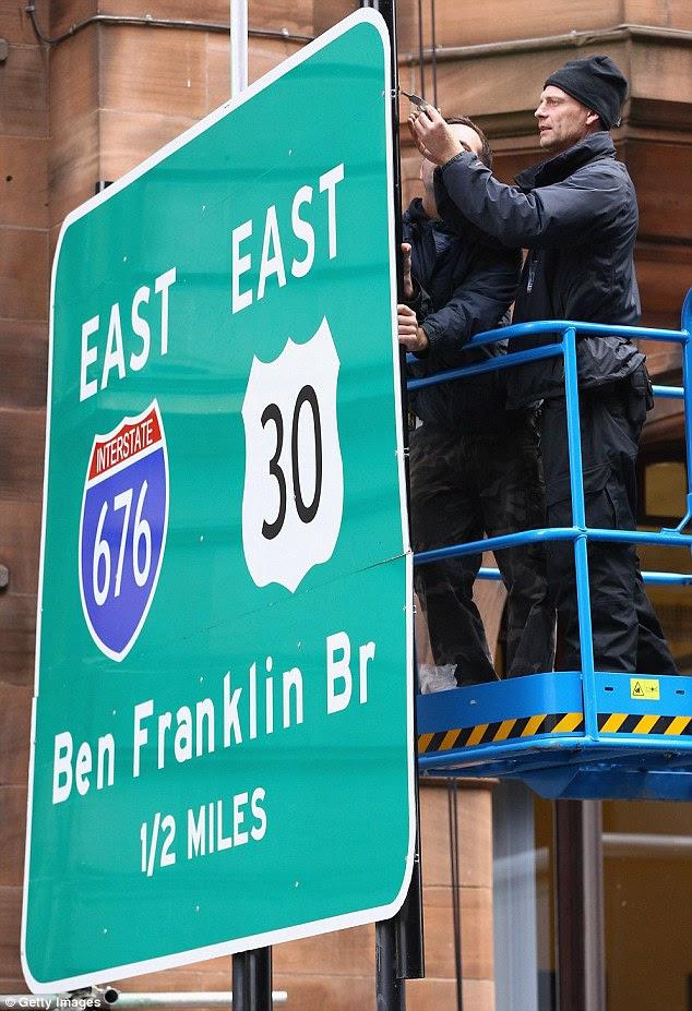 Landmark: Workers put up signs for Philadelphia's famous suspension bridge