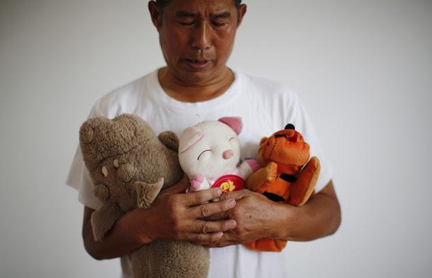 Zhang Yongli, cuja filha Zhang Qi estava no voo MH370, abraça os brinquedos da menina enquanto posa para foto em Pequim, em 22 de julho (Foto: Kim Kyung-Hoon/Reuters)