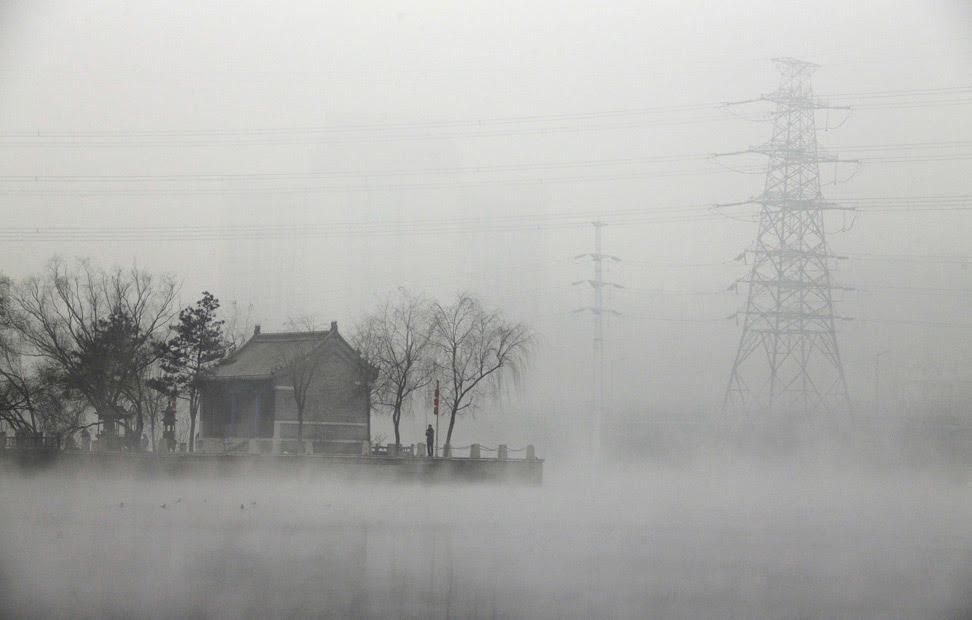 Un hombre pesca cerca de un templo, al lado de un río, en una mañana cubierta de polución, en Pekín.
