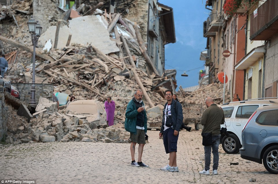 Residents and photographers stand next to damaged buildings after the strong heartquake hit Amatrice