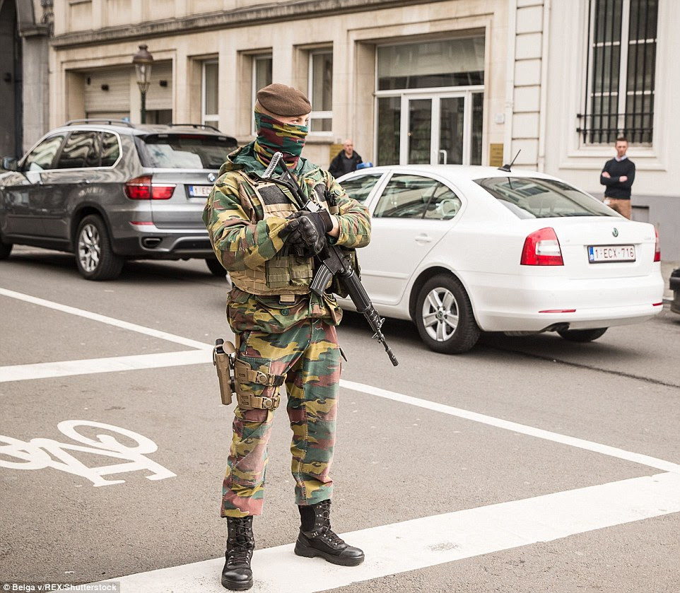 Armed presence: A soldier with his face covered guards a road near the Maalbeek subway station as they try to stop any further attacks