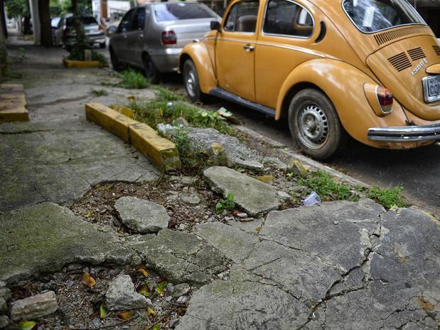 Na rua Arizona, buracos e obstáculos prejudicam a circulação de pedestres em uma calçada. Foto: Fernando Borges / Terra