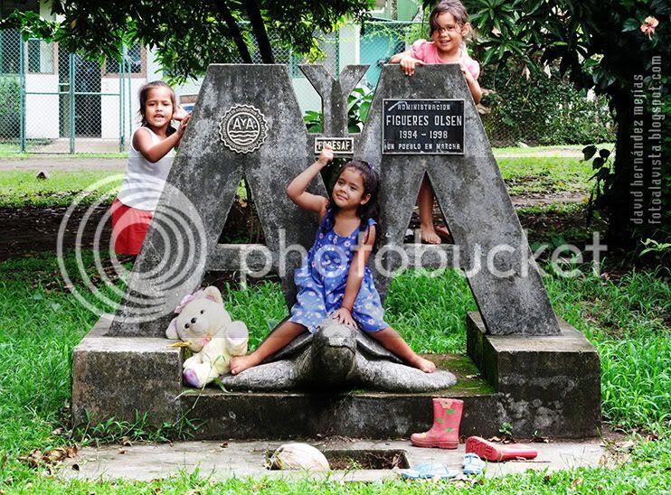 Tres niñas en Tortuguero juegan sobre un elemento conmemorativo del pueblo