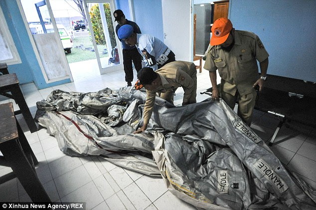 Rescue workers display the uninflated escape slide from flight 8501 at Pangkalan Bun airport in Indonesia